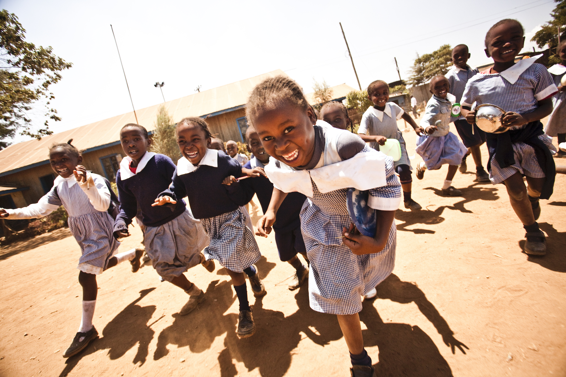 Children smiling and running in a playground in Kenya.