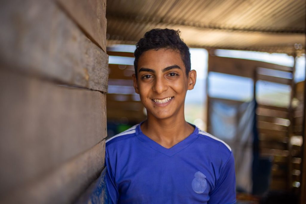 A teenage boy stands in a wooden shack. He smiles, happily.