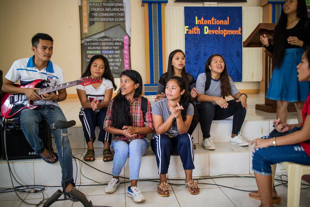 A group of 5 girls sits on the steps of their Compassion centre singing along to someone playing guitar