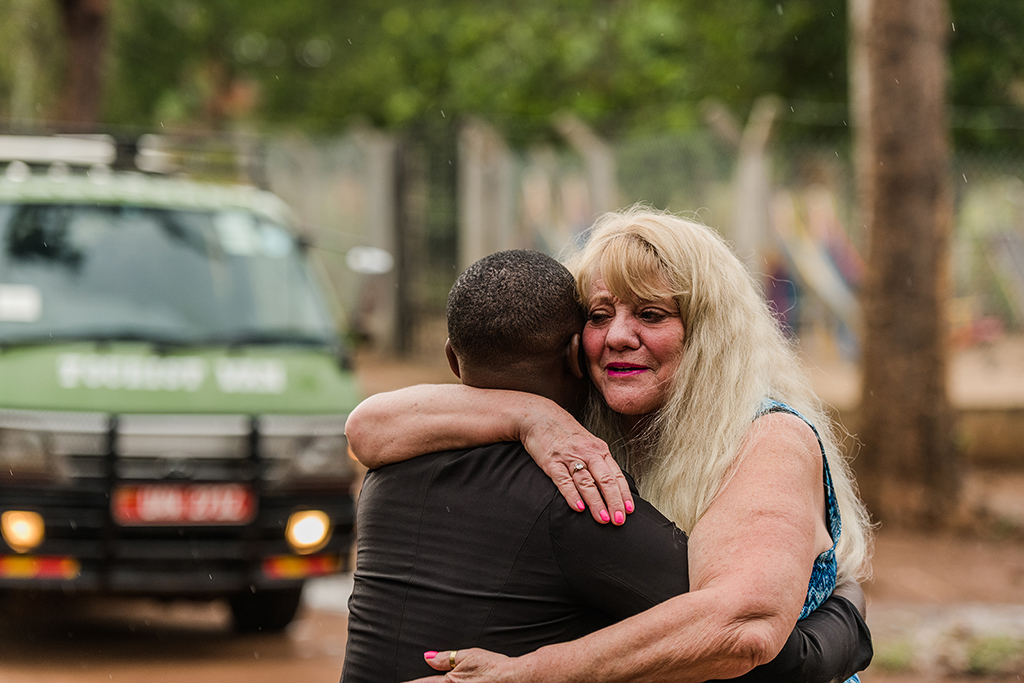 Cynthia hugs the young woman that she and her husband sponsor in Uganda.