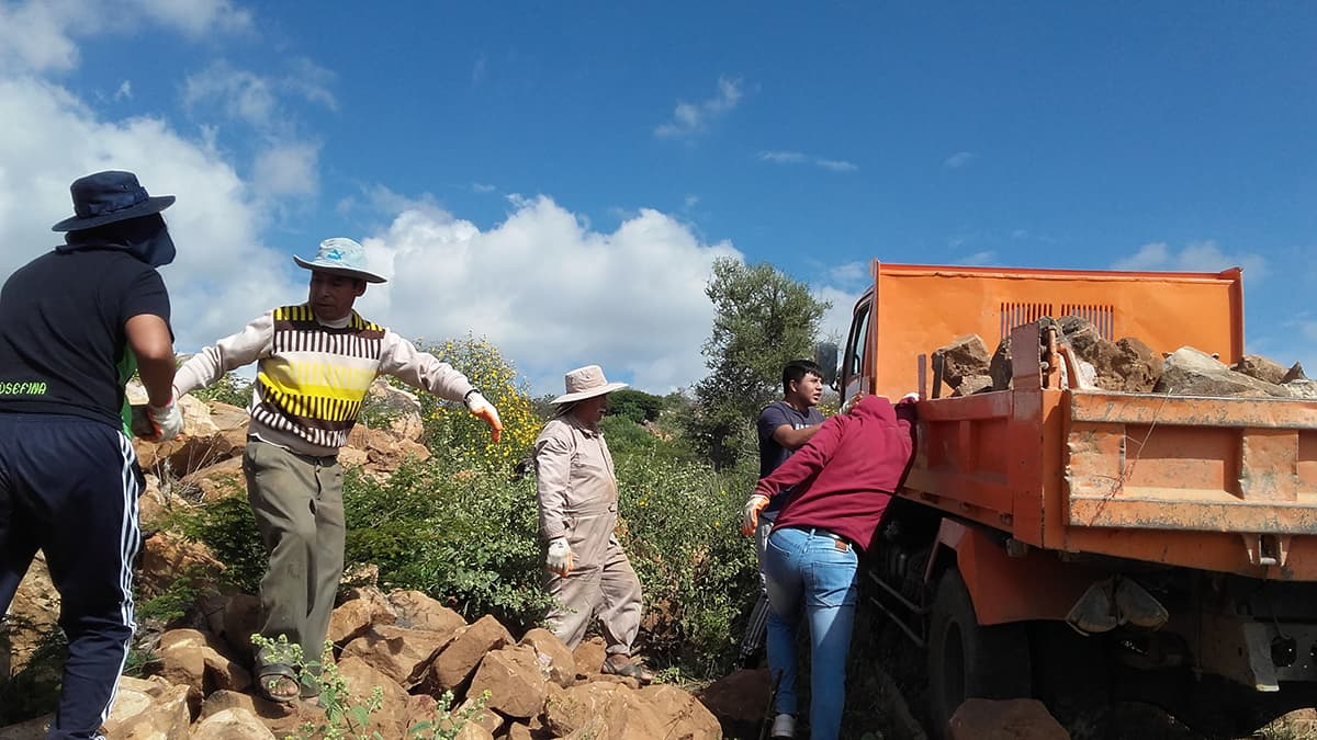 Workers carry stones to the property