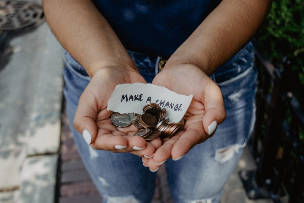 """Girl holds change in her hands with a note that says, """"Make a Change"""""""