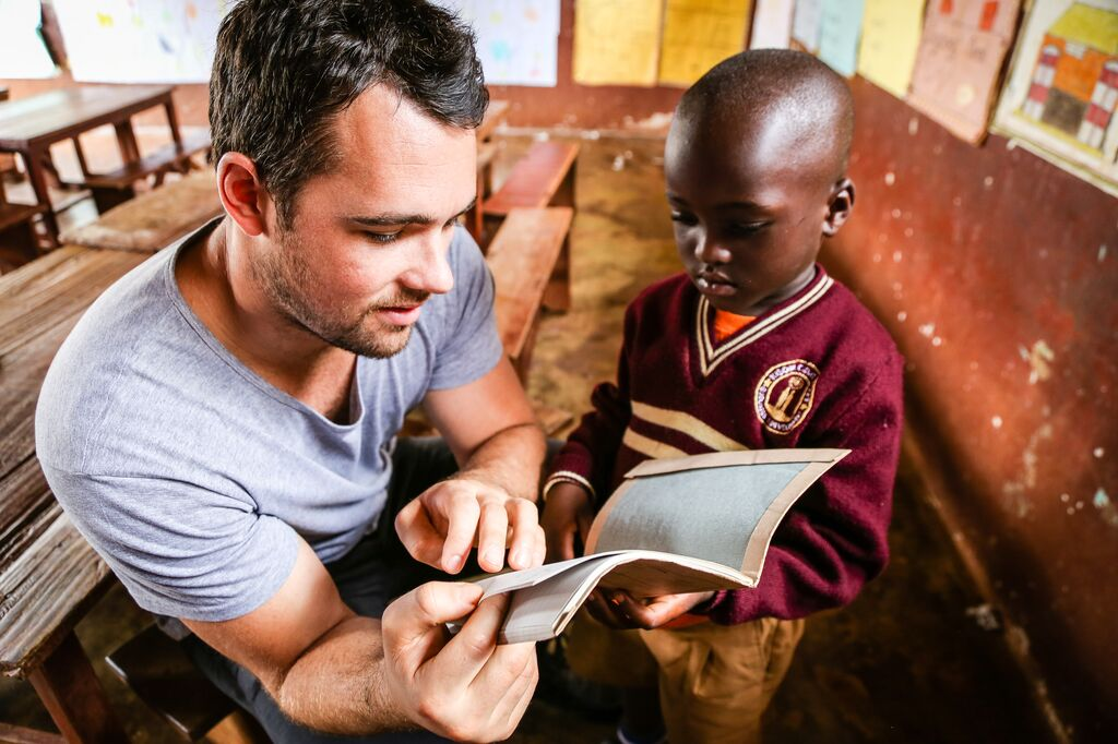 Sponsor is visiting his child and reading a book to him.