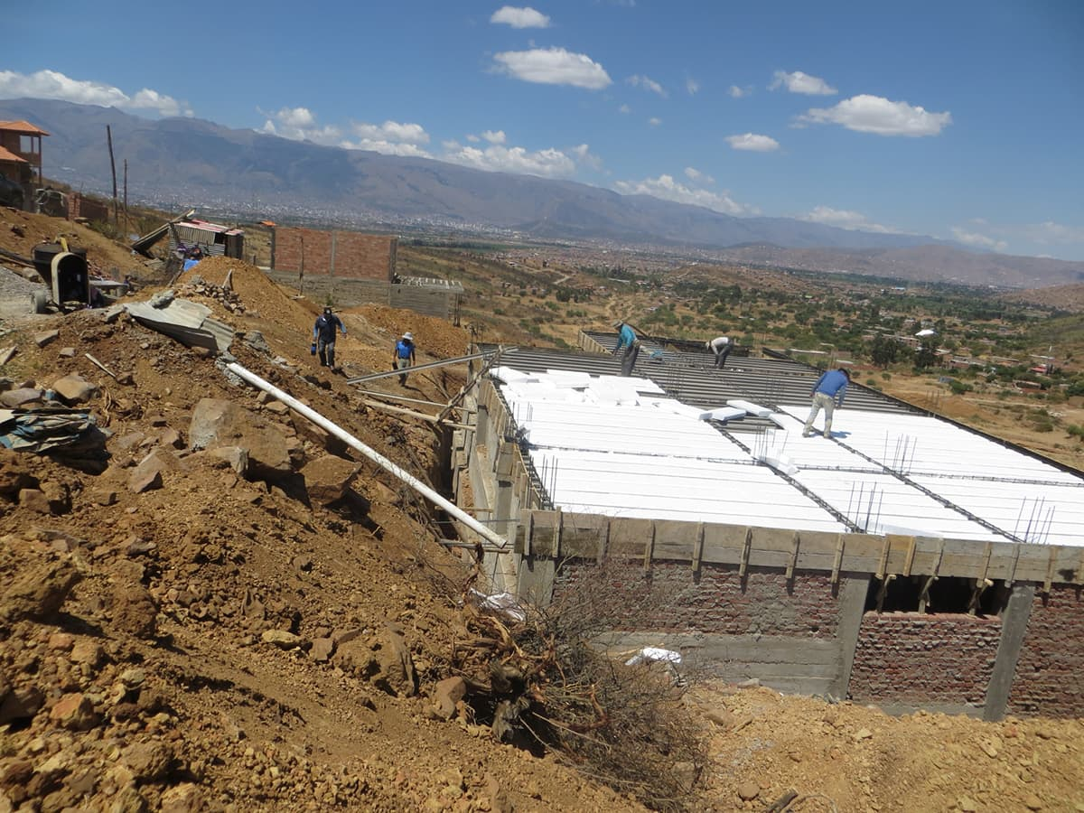 Another angle of the construction site showing preparation second floor joists and insulation.