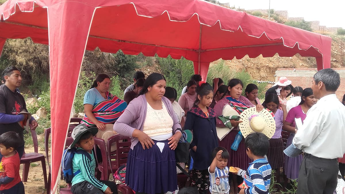 Women men and children sit and stand under red, temporary awning, set up for an outreach program. A man stands in front of the them and speaks.