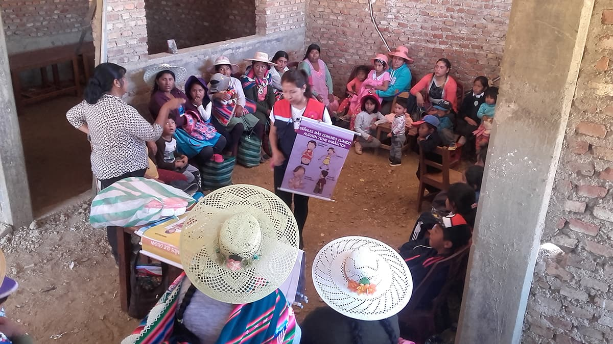 A group of moms sit in circle in a cinder block building and listen to center volunteers teach. Many wear traditional Bolivian garb.