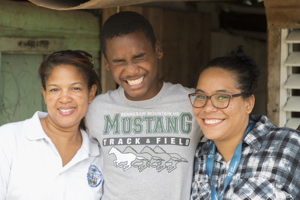 Esperanza, Julio and Isabel pose for a close-up photo of the three of them smiling.