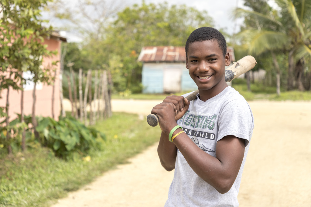 Julio smiling and posing with a baseball bat over his shoulder.