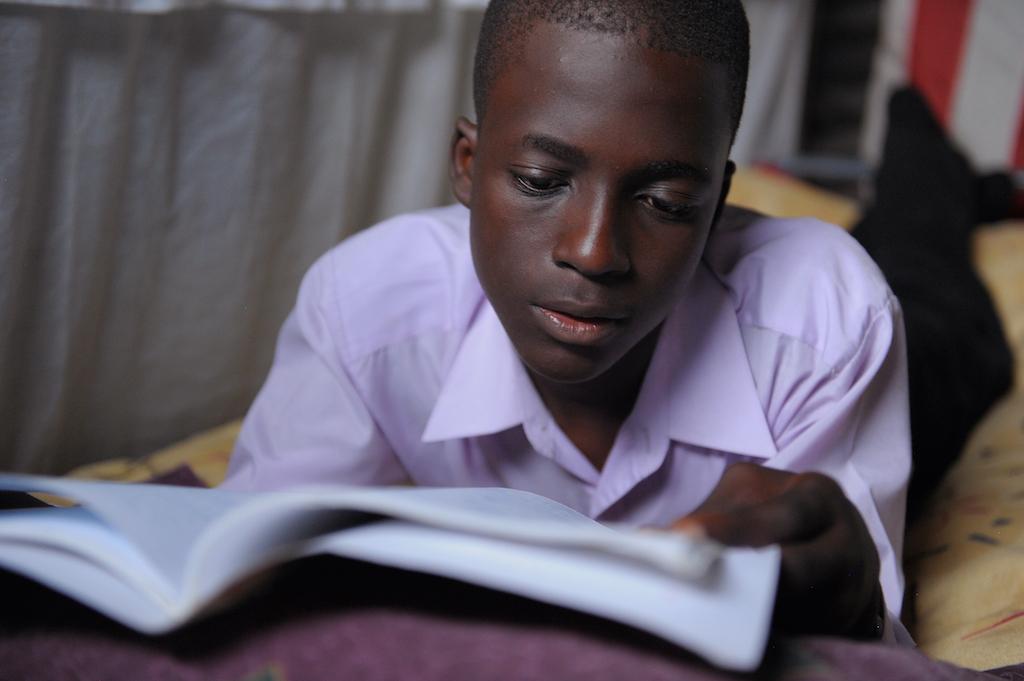 A teen boy reading a book.