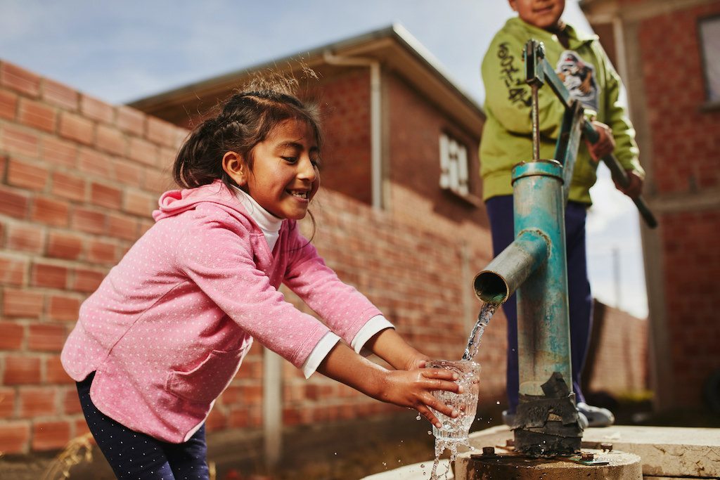 A young girl getting clean water from a borehole pump.