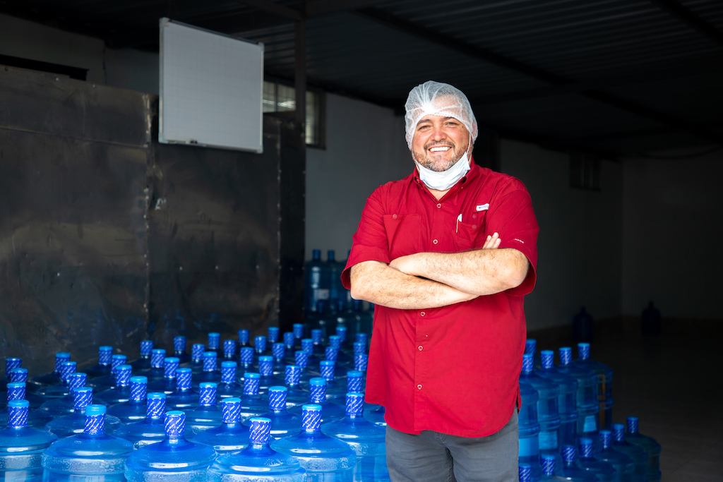 Santiago poses in front of several containers of water.