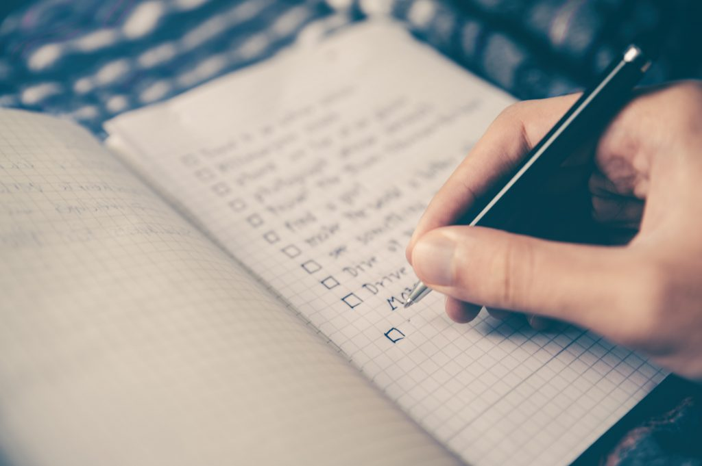 Someone writing a to-do list in a notebook.