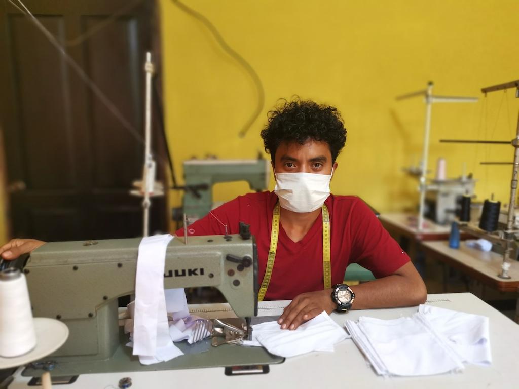 Yonatan sits at a sewing machine, wearing a mask.