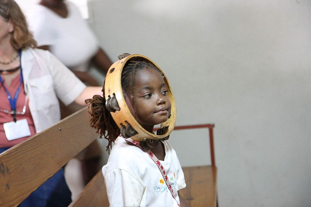 Little girl smiles with a tambourine on her head