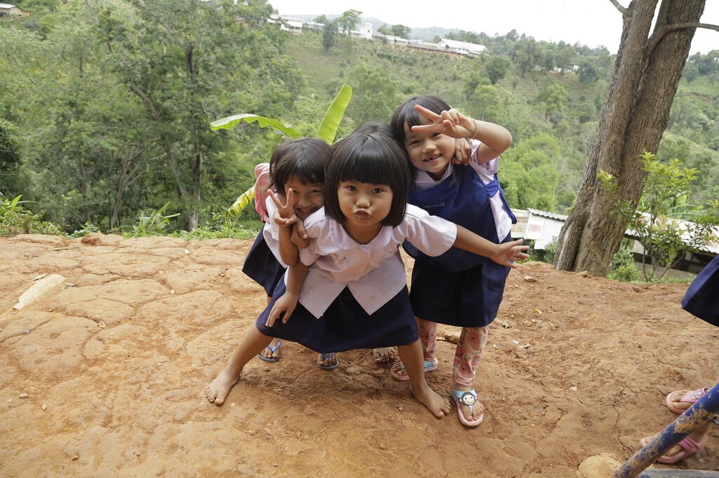 Three little girls pose with peace signs for the camera
