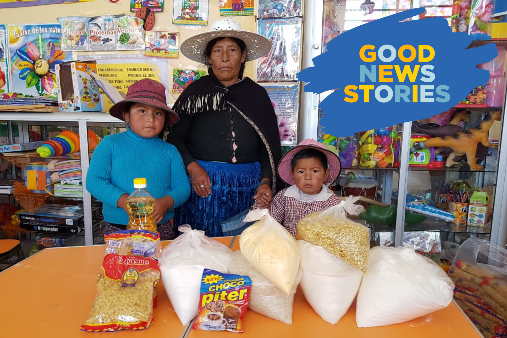 A woman and two children pose with a grocery delivery provided by Compassion.