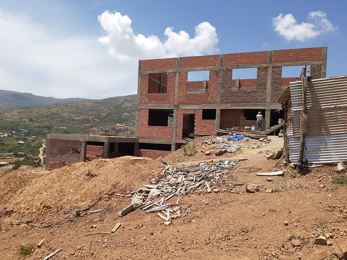 Photo of building with finished concrete and brick walls. Behind it a valley stretches out below.