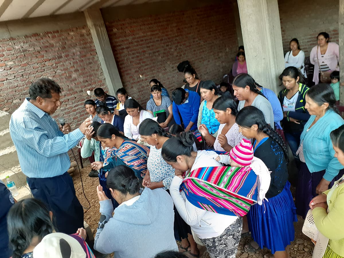 Women gather in the unfinished church building to at church evangelistic meeting. They bow their heads and pray with the pastor.
