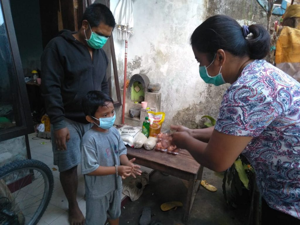 A Compassion staff shows a young boy how to wash his hands effectively. Both are wearing masks.