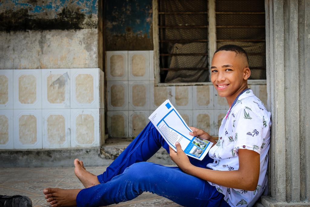 A teenage boy reads a letter from his sponsor.