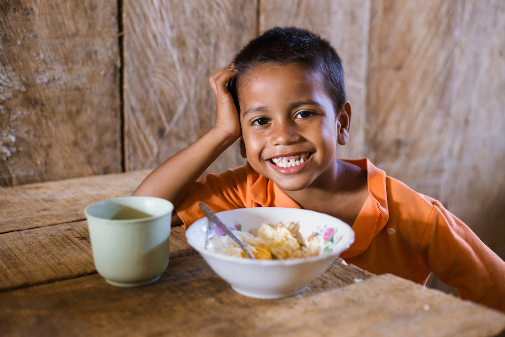 A boy smiles with a bowl of food on the table in front of him.
