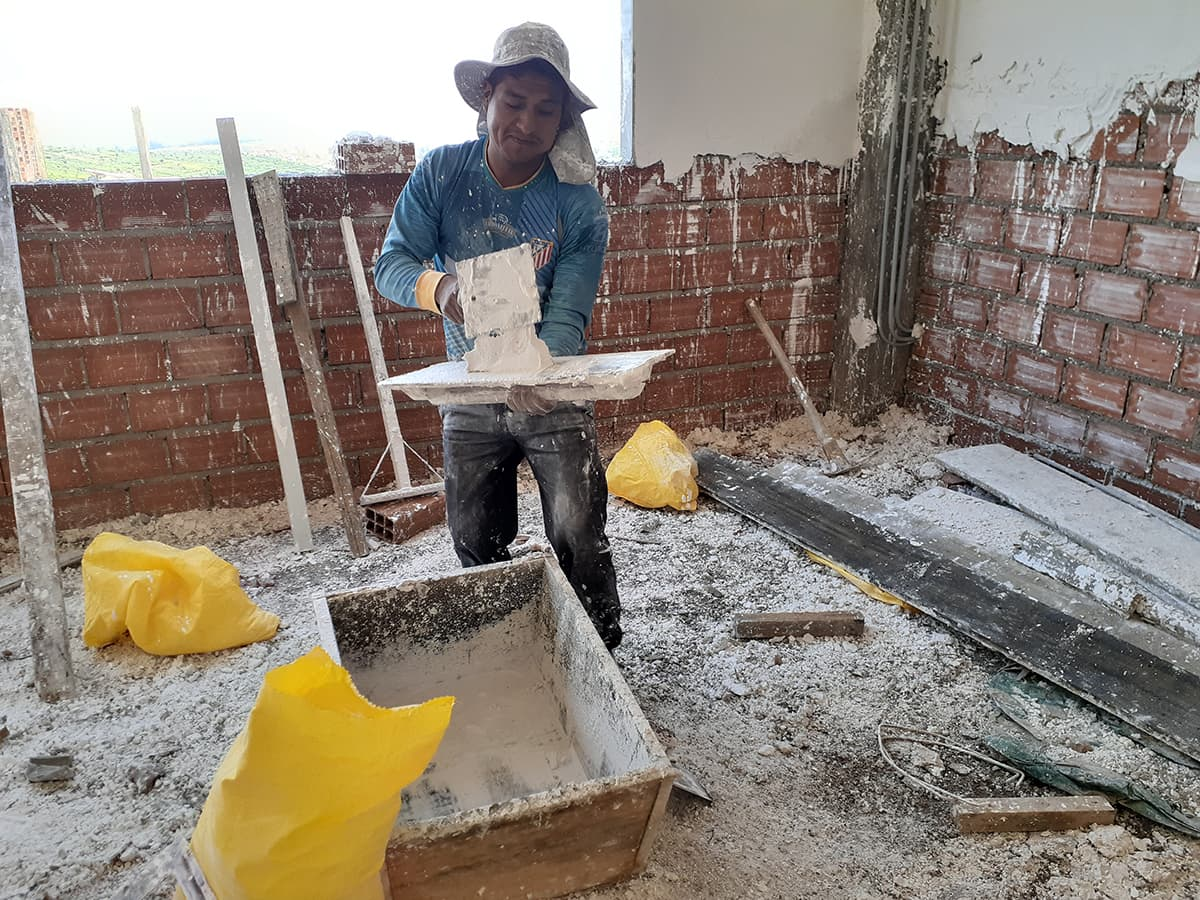 A worker holds a plaster pallete and knife, preparing to spread plaster on the walls.