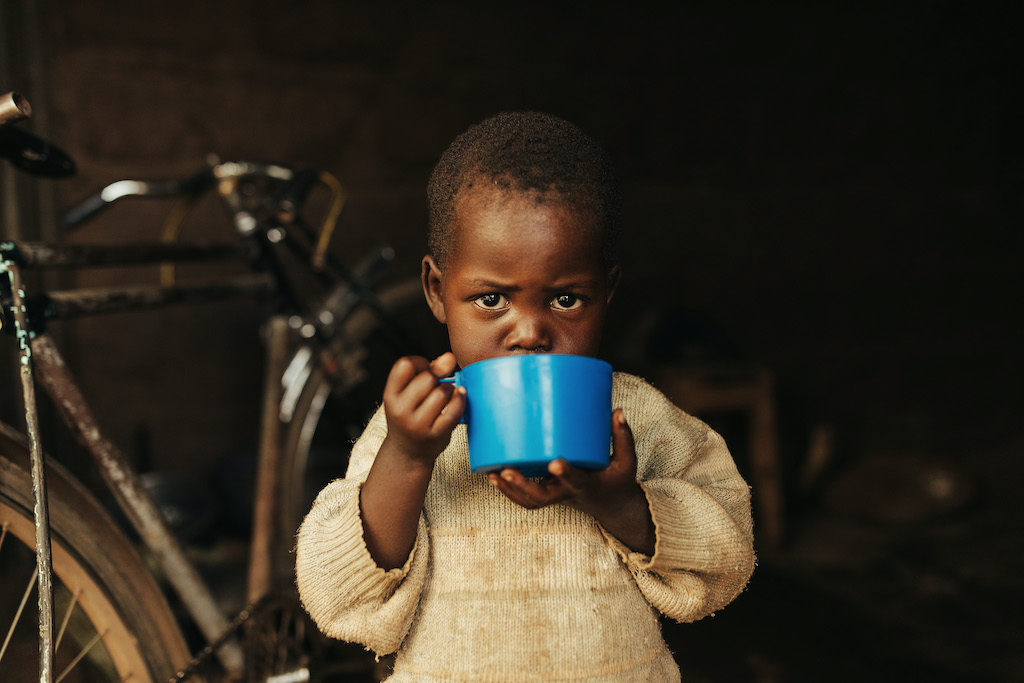A photo of a Kenyan toddler drinking from a mug.