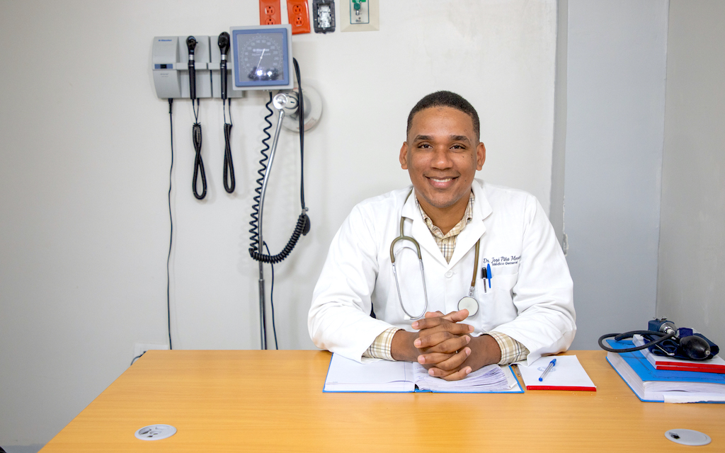Jose sits at his desk wearing a doctor's uniform.