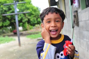 A young Guatemalan boy holding a toy car