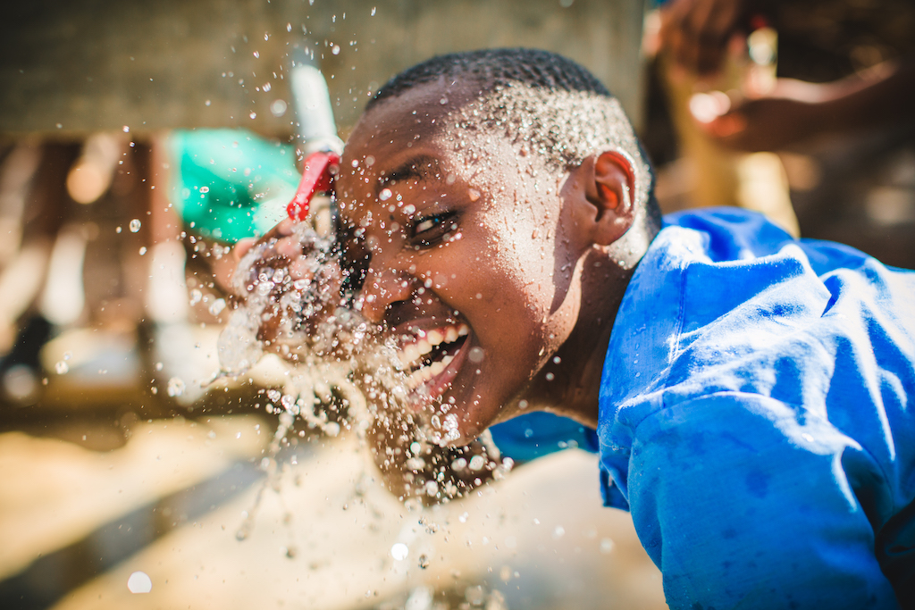 A boy drinking from an outdoor tap in Tanzania