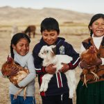 Three children carrying chicken and a goat in Bolivia