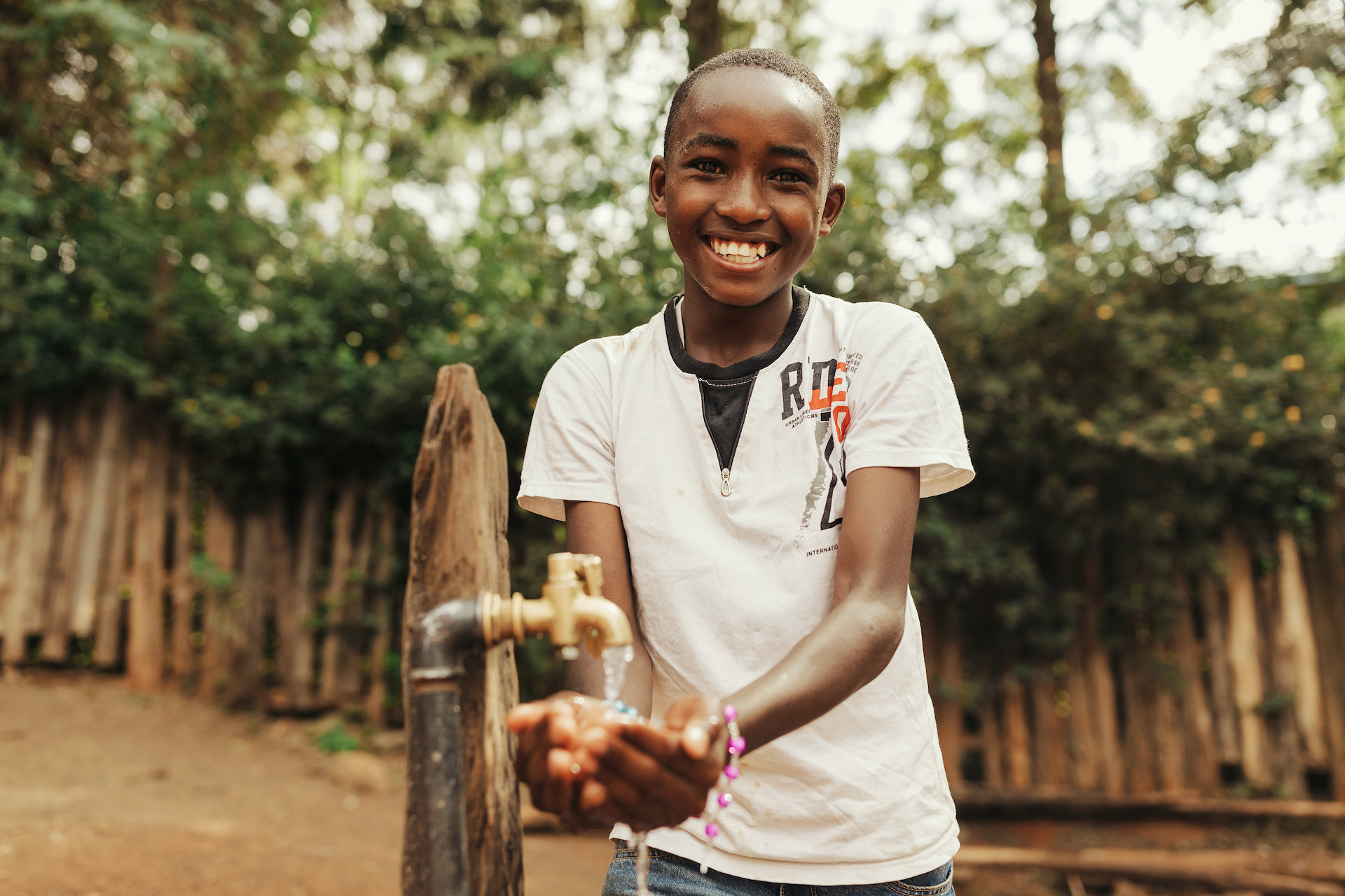 A boy getting water from an outdoor tap