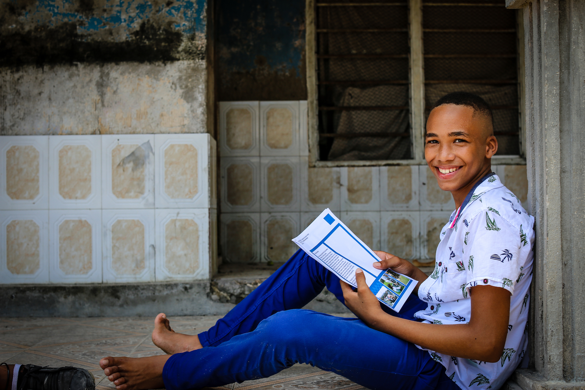 A teenage boy in Colombia sits on a ledge reading a letter from his sponsor.