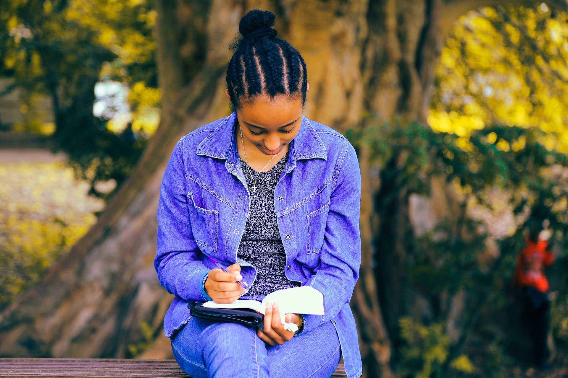 A woman sits under a tree writing in a journal.