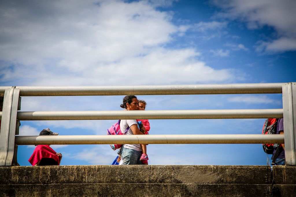 A woman carrying a toddler crosses a bridge at the Venezuela-Colombia border.