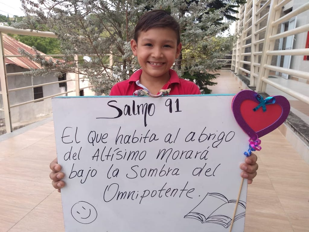 A boy holding a poster with Psalm 91:1 written on it in Spanish