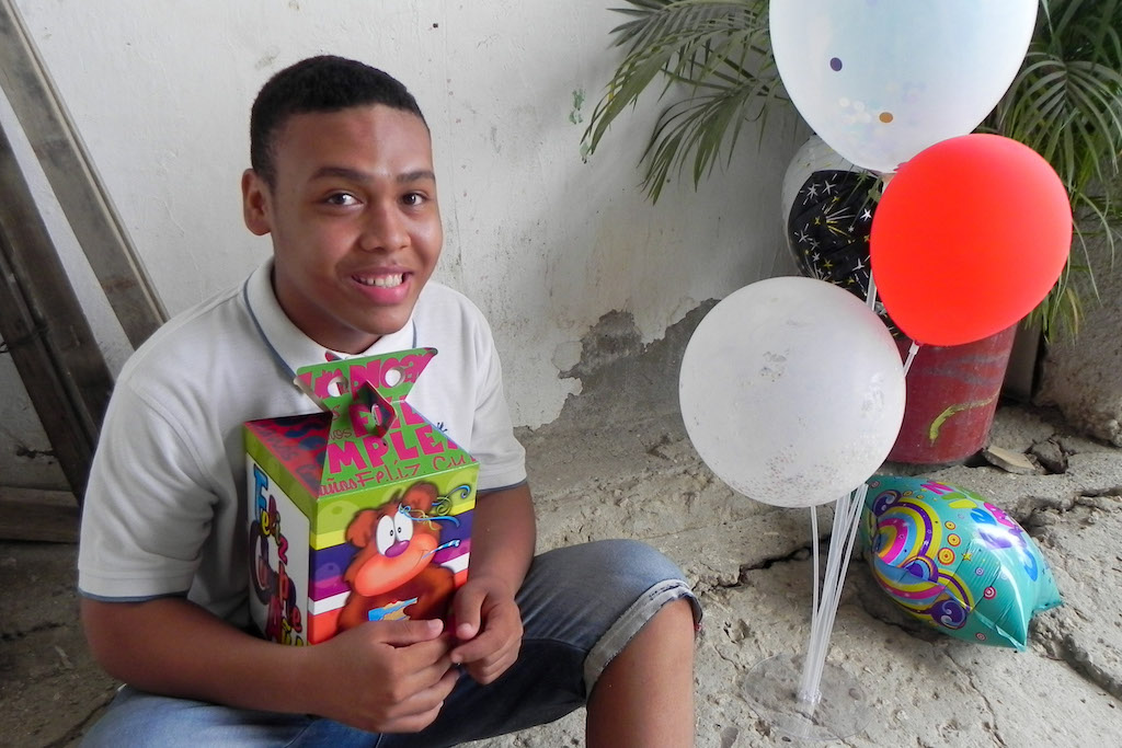 A boy poses with his birthday gift and balloons