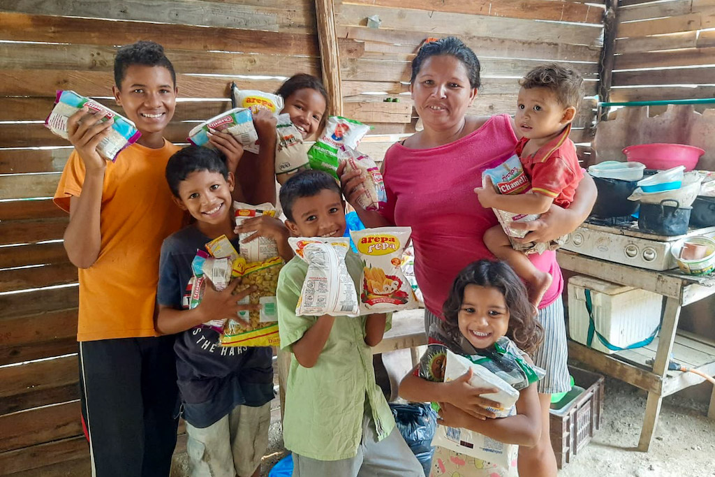 Gladys and her children with the groceries bought for them by the Compassion centre.