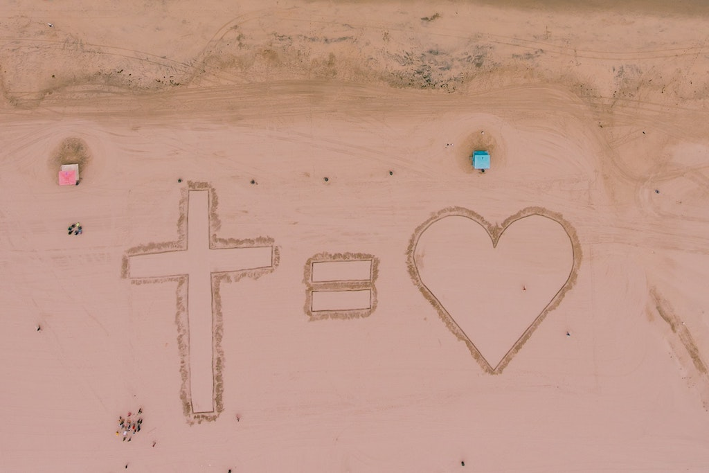 "A ""cross equals heart"" symbol written in sand on a beach."