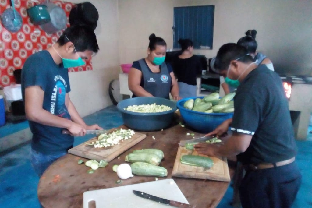 Compassion staff stand at a table chopping vegetables.