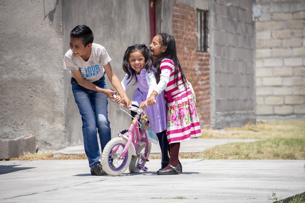 Three children laugh and play with a bicycle.