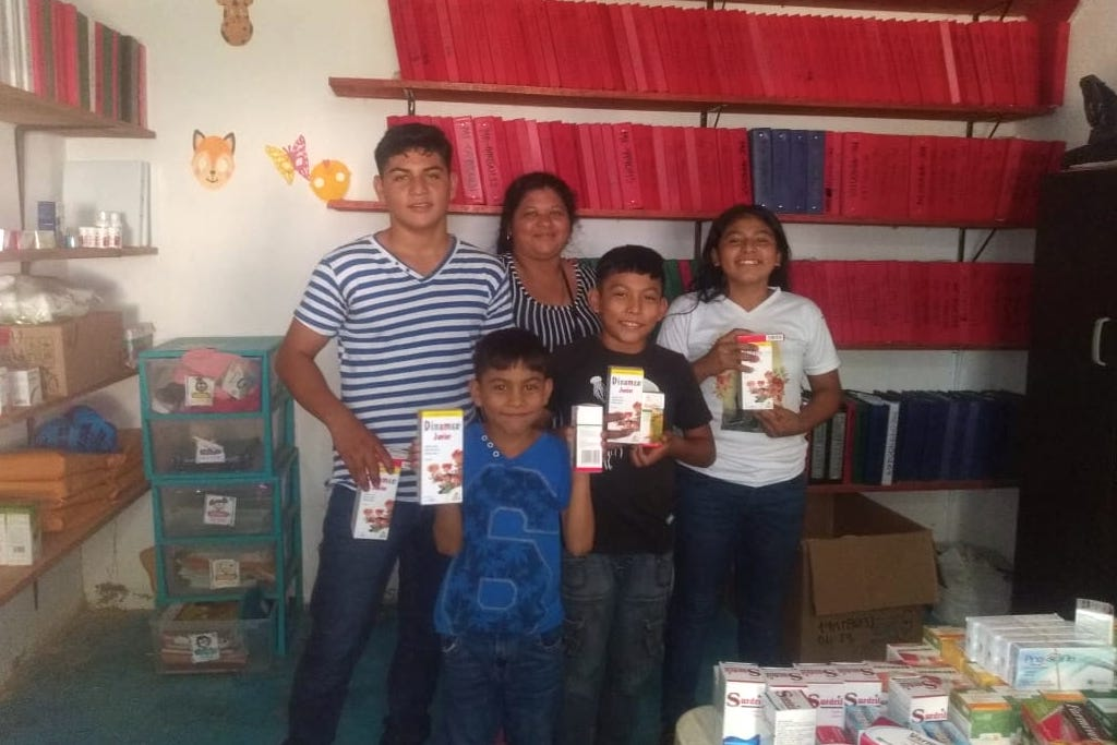 A family posing with vitamins, in the Compassion centre office.