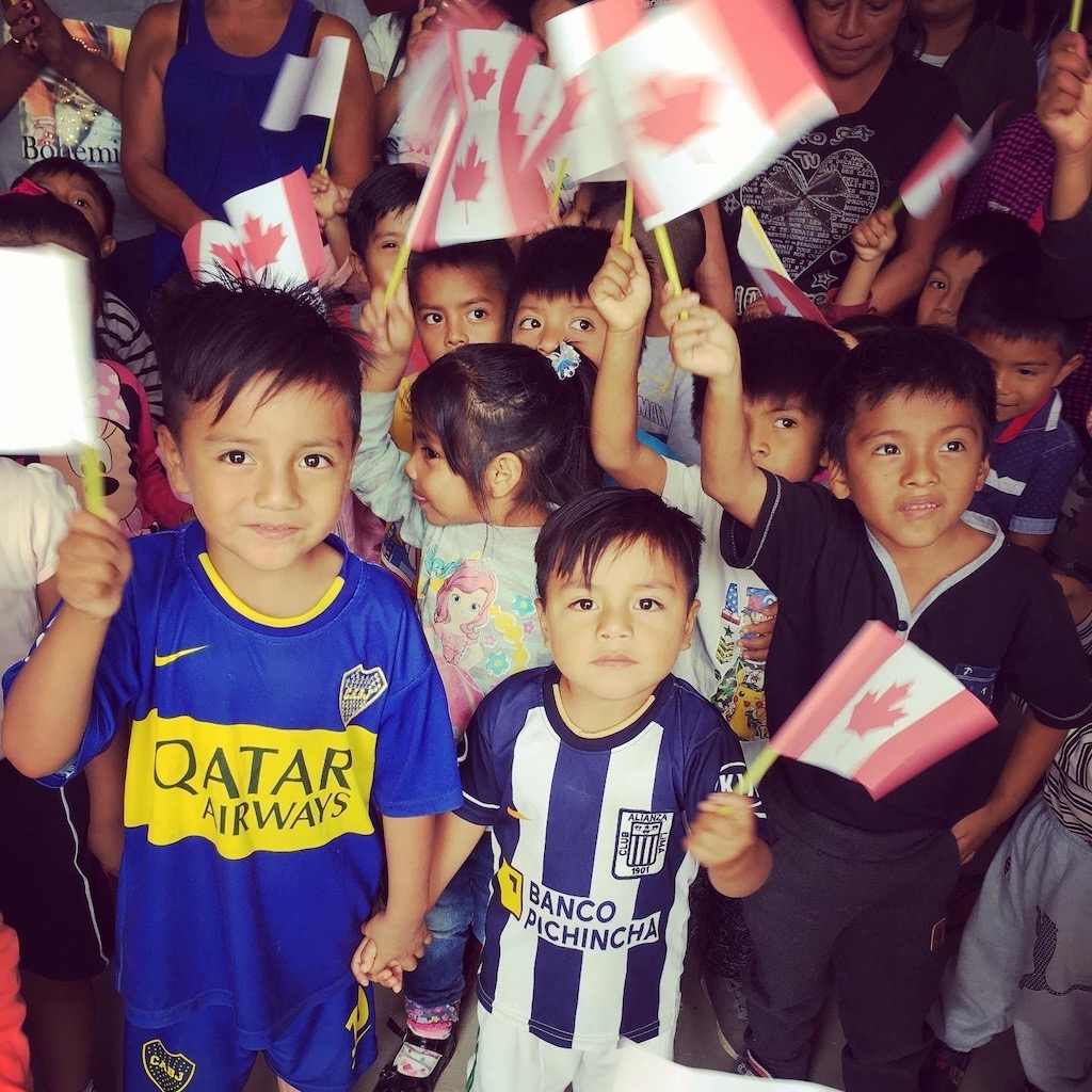 Children from Ecuador wave Canadian flags