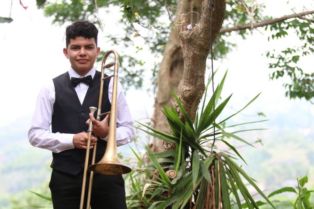 A teen boy poses with his trombone