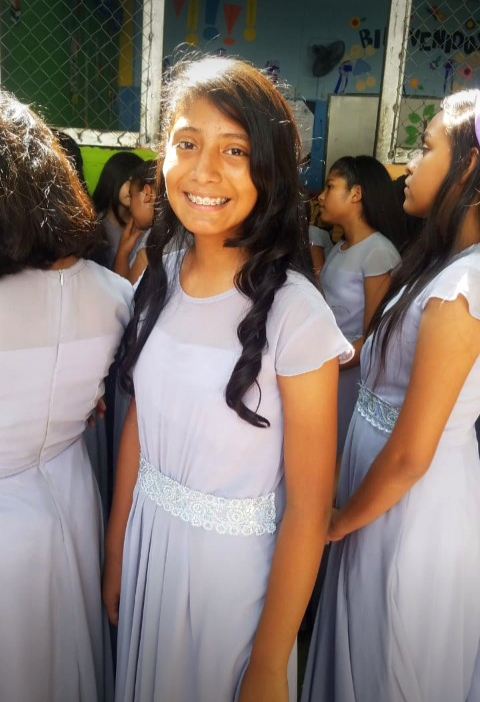 Young teen girl stands and smiles wearing a purple dress.