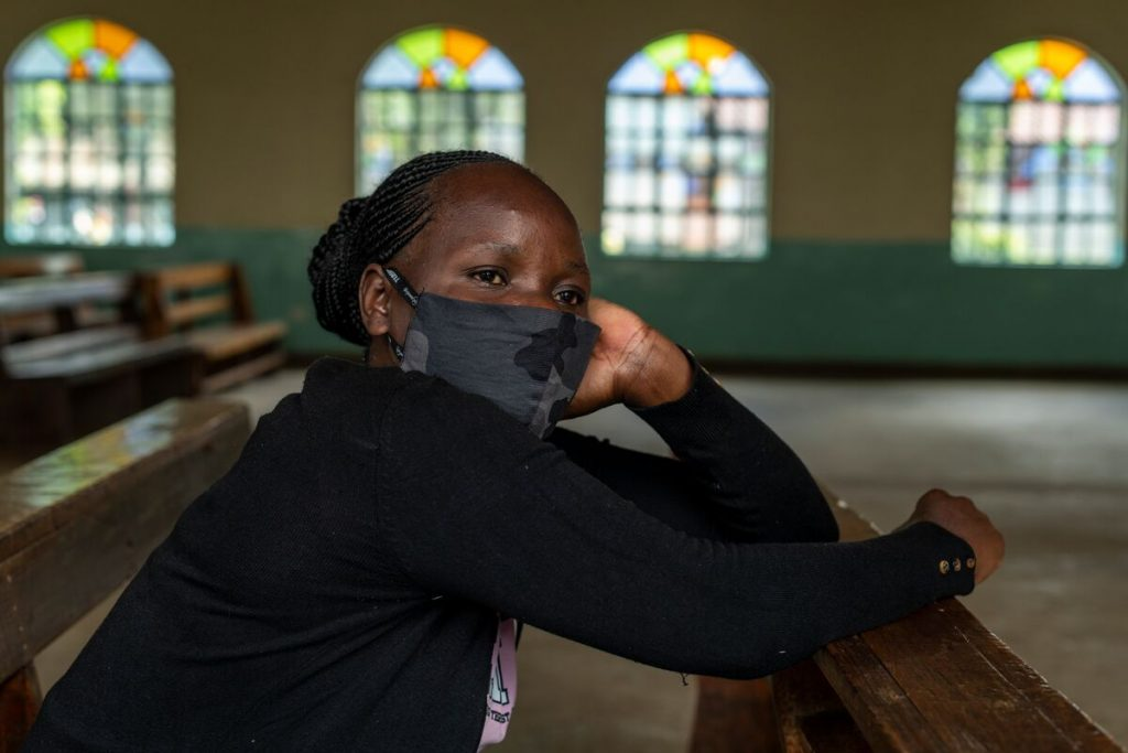 Woman wearing a mask in a church leans over a church pew looking subdued.
