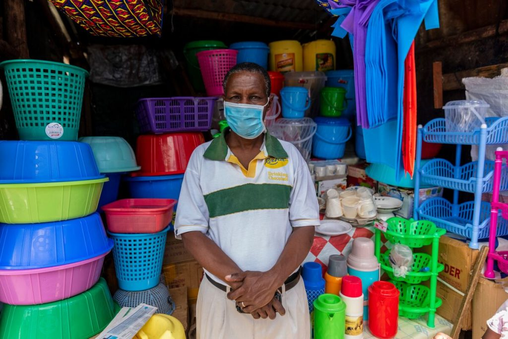 Man wearing a blue mask stands in front of a pile of colourful baskets