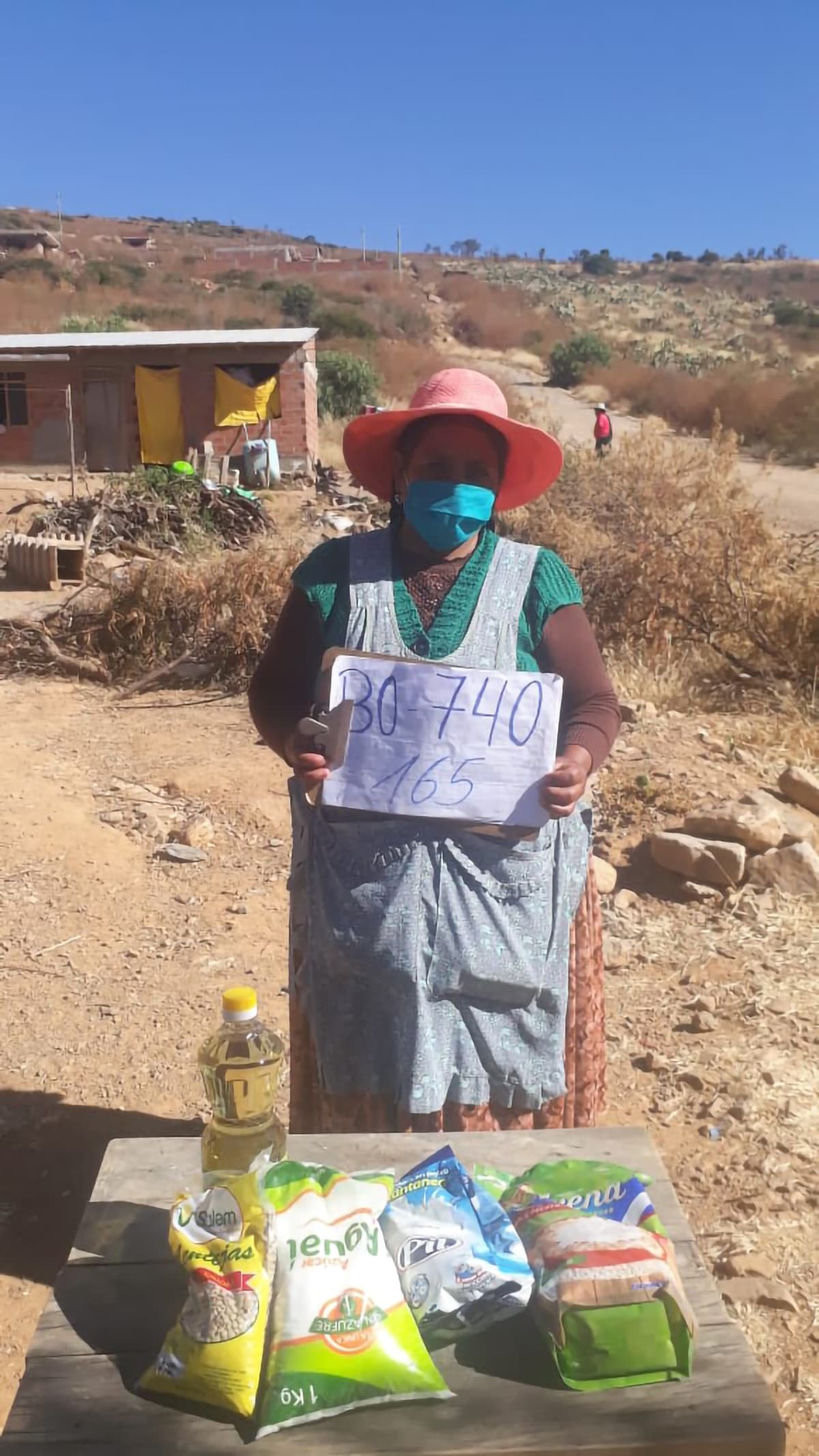 A Bolivian woman stands out side. She wears a surgical mask and stands behind hygiene kit layed out on the table.