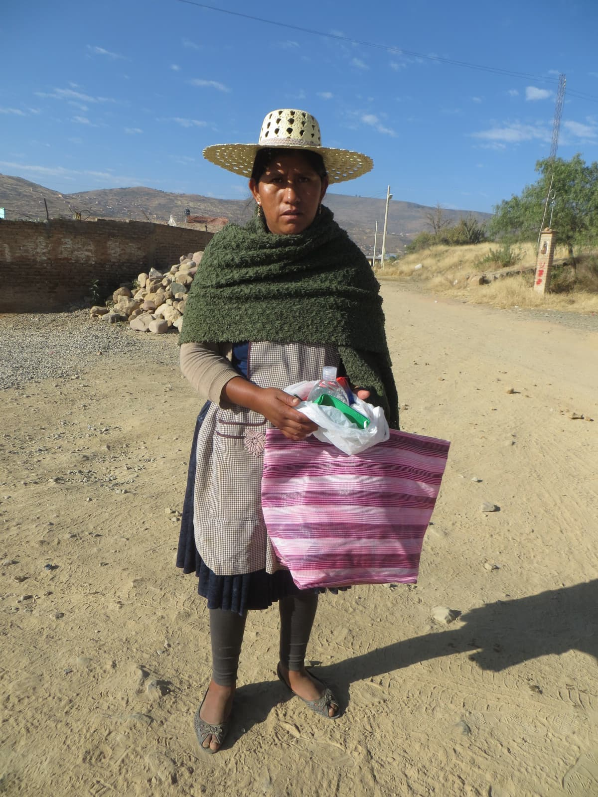 A Bolivan woman, wearing a traditional hat, holds a bag containing a hygiene kit. She stands outside.