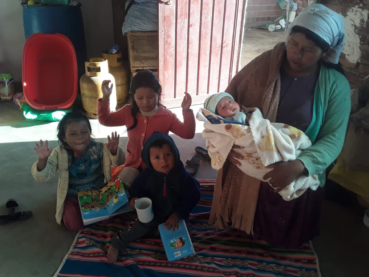 A Bolivian woman kneels down and prays. She holds a young baby and three other children kneel and pray beside her.